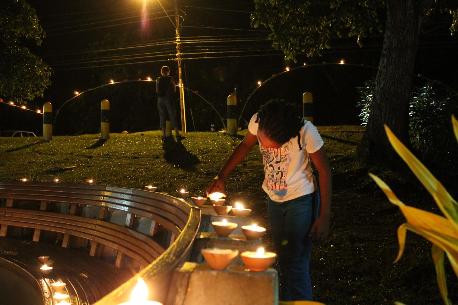 A young girl lights a deya during Divali