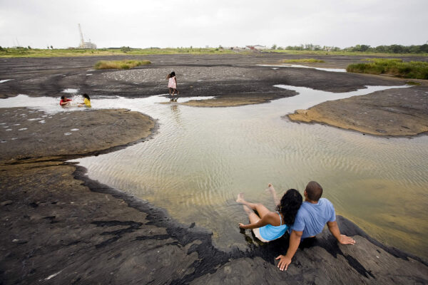 A couple relaxing in a sulphur pool at the La Brea Pitch Lake